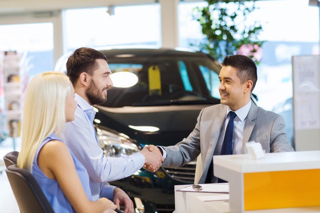 couple qui sert la main à un bailleur de leasing voiture